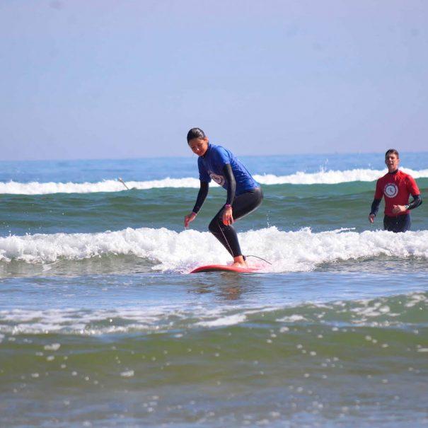 niña puesta en pie espuma surf los locos surf school copia
